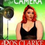 A fulsome bodied redhead stands in front of a green screen and some camera equipment. She's wearing a black body and is posing. Title: Flirting with the Camera. Author: Ros Clarke.