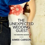 A bride caucasian bride is seen from the chest down, pressed against a wall by a man in a blue shirt and jeans.