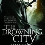 Book cover for The Drowning City by Amanda Downum. A cloaked figure stands in the shadows in a forest. A sword hand peeks out from behind them.