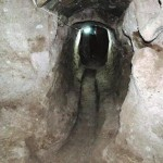 A view of a dimly lit tunnel crudely cut from light colored stone.