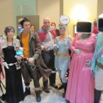 """A group of 6 people cosplaying as characters from the comic Saga. The prince and his wife are dressed like 19thc aristos but with tv monitor heads. Lying cat is a white woman in a grey catsuit holding a sign that says """"lying."""" The Will is a bald white man wearing a red cape with dark pants and light shirt. Marko has goat horns and wears an orange shirt with brown pants and trench coat. Alana is a white woman with fairy wings who wears a long black dress and holds a baby doll. Izabel the ghost girl is a white woman in a pink wig and dress and black tights."""
