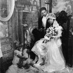A young black couple poses for a wedding photo in the 20s or 30s. He wears a dark tux with a white shirt and she wears a tea length white gown with a full length lace veil and sits in a chair holding a large bouquet. At their feet is a ghost image of young children suggesting the future children of a happily married couple.