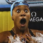 A black woman in a pool up to her shoulders wears a blue swim cap with her goggles on her head. Her hands are on her chest, and her eyes and mouth wide-open in delighted surprise,