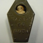 """A Victorian-era antique. A small olive green metal coffin. A glass window reveals the simple face of a small doll. A raised inscription reads """"don't talk so much"""""""