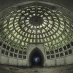 Greenish light filters through a steel and glass dome under a lake.
