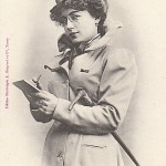 """A black and white photo from 1902 of a woman journalist """"in the future"""". A white woman holds a walking stick in the crook of her elbow and a pencil and notepad in her hands. She wears a trench coat and a top hat sits on her dark, curly hair."""