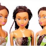 Three vinyl fashion dolls like Barbies have long brown kinky hair, darker skin and wear African print clothing.