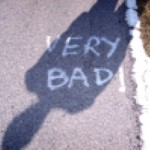 """Meoskop's twitter avi: a patch of asphalt pavement with """"VERY BAD!"""" spray painted in whitee. A person's long shadow stretches from the bottom left to upper right corner of the image."""